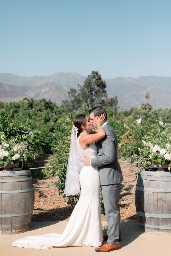 a vineyard wedding ceremony in the vines, with barrels with white florals and greenery is a cool idea not only for a fall wedding