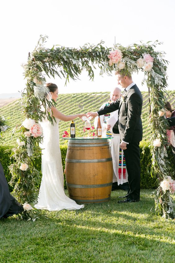 a vineyard wedding ceremony with a greenery and pink flower wedding arch and a barrel with wine bottles and wine glasses