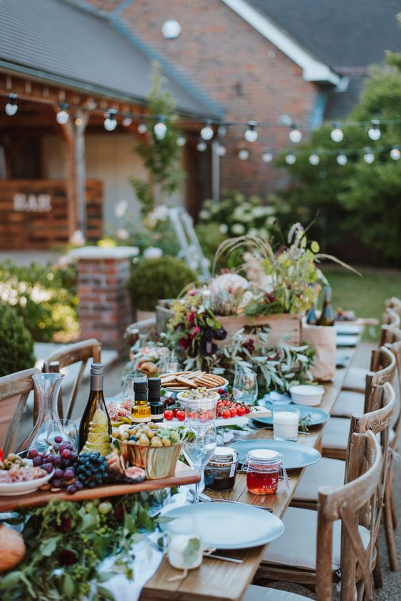 a vineyard wedding reception with a cozy and homey feel, with greenery, blooms and lots of wine and grapes is amazing