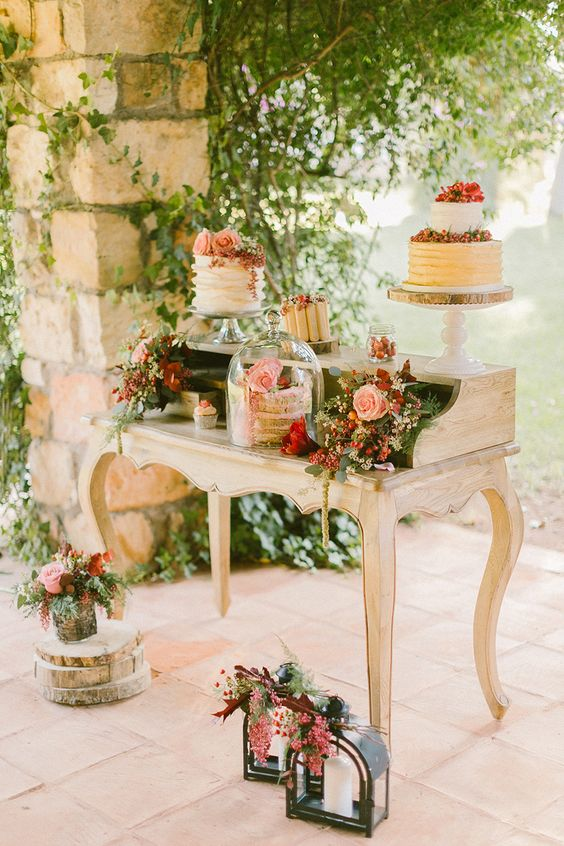 a vintage dessert table decorated with greenery, pink and red flowers and chic stands and a cloche
