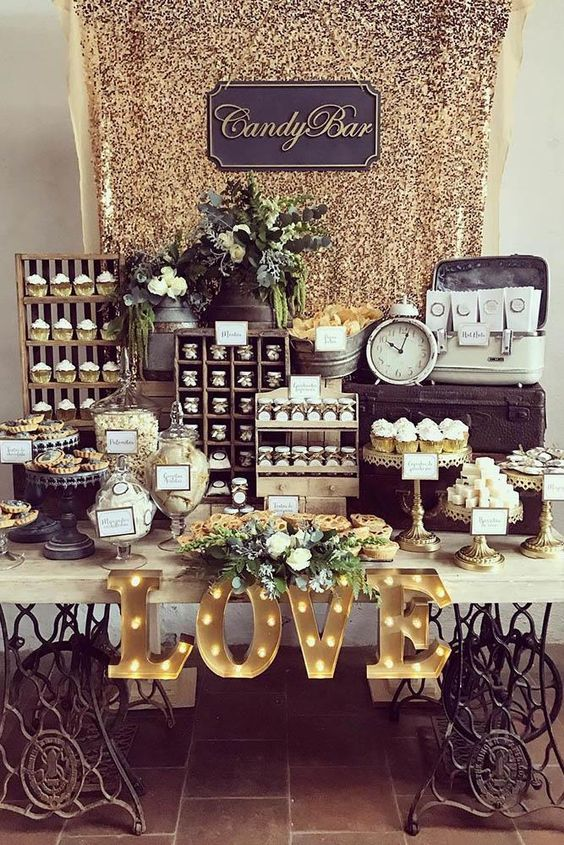 a vintage sweets table with marquee letters, jars with lids, wooden shelving units for sweets and a glam gold sequin backdrop