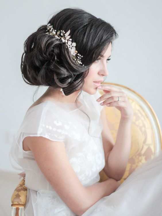 a voluminous curly side updo with some locks down and a statement embellished floral hairpiece that rocks