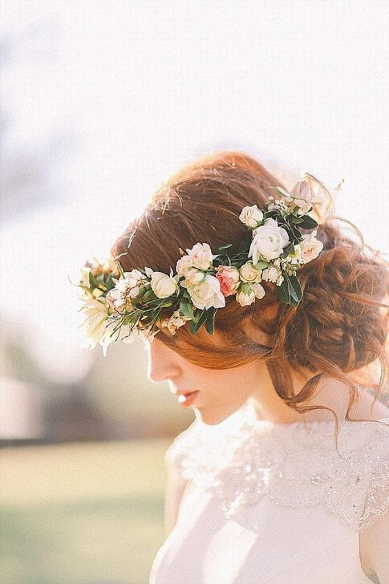 a wavy and curly side bun with some waves down and a fresh flower crown for looking boho and romantic