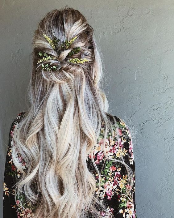 a wavy half updo with a volume on top, twisted greenery decorated element and waves down