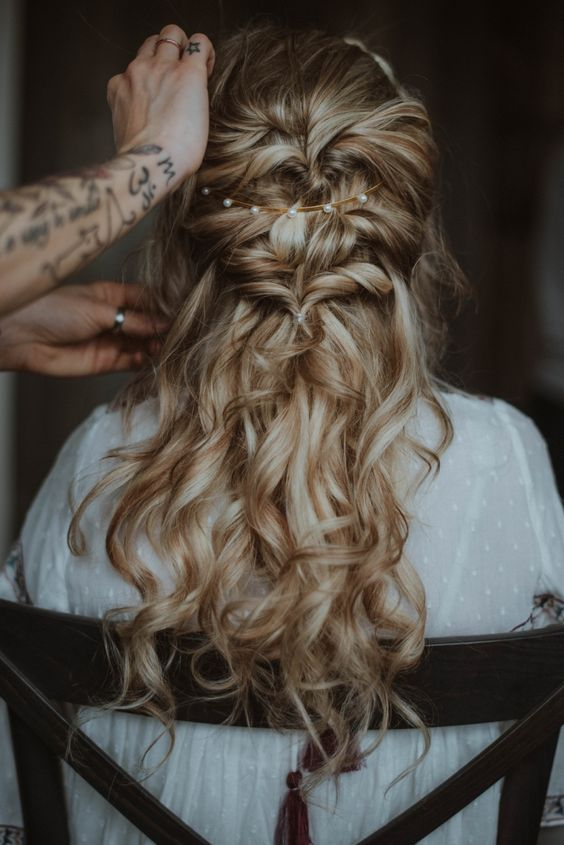 a wavy twisted half updo with a messy top, a pearl headband and waves down is a chic and romantic idea
