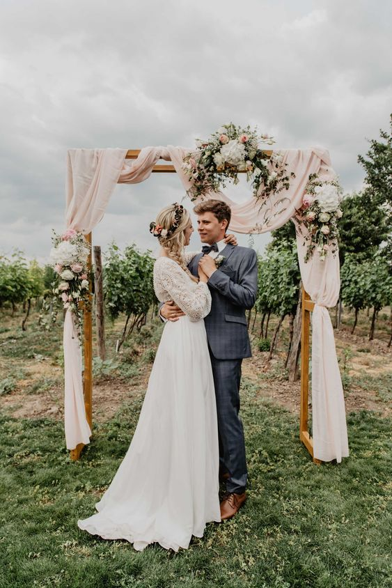 a wedding arch placed right in the vines, with pastel pink fabroc, neutral and blush blooms is a lovely idea for a vineyard wedding
