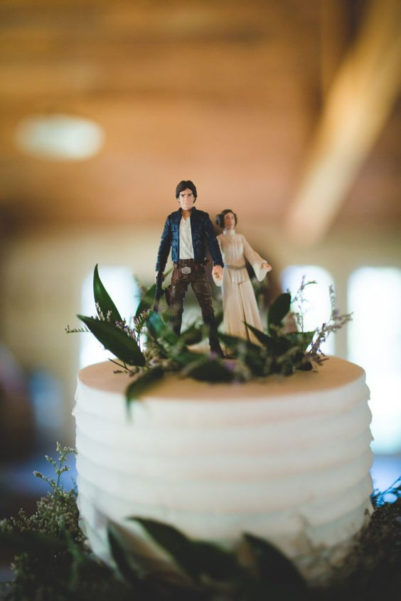 a wedding cake topped with greenery and wildflowers plus figurines of Leia and Han solo is a cool idea