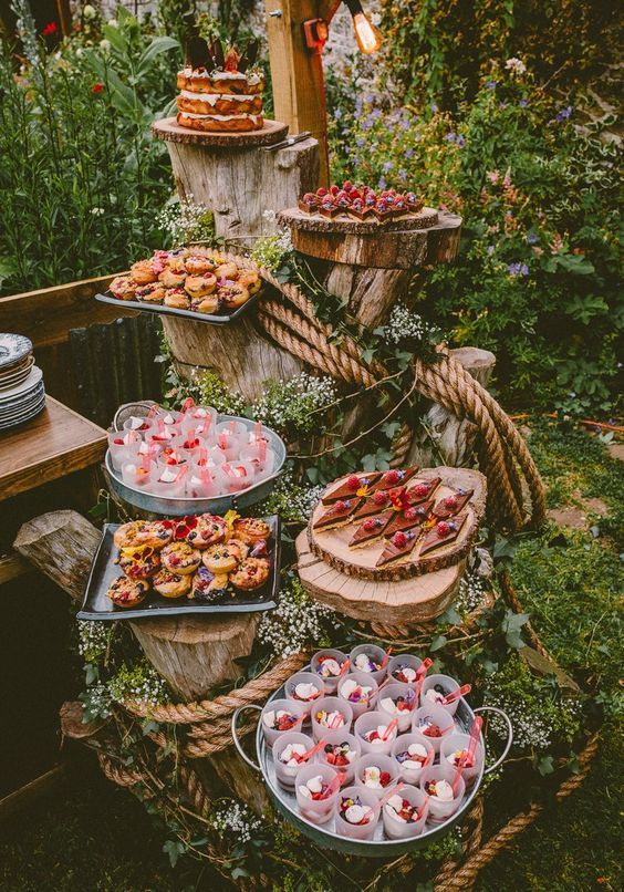a wedding dessert display of tree stumps decorated with greenery, blooms and ropes and wood slices as sweets stands