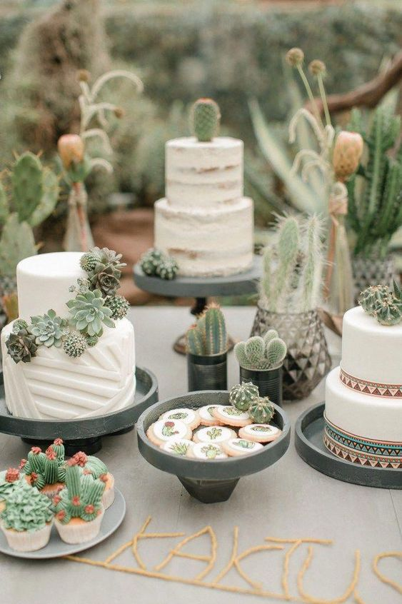 a wedding dessert table all done with succulents and cacti covering the sweets, placed here in pots and cacti and succulent sweets