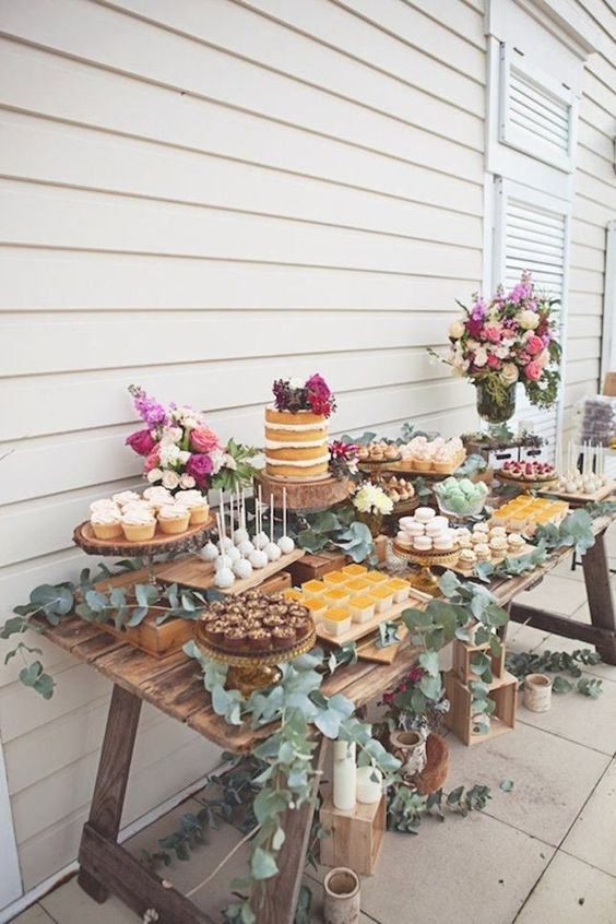 a wedding dessert table of a rustic weathered wooden table decorated with eucalyptus and bright flowers and delicious desserts