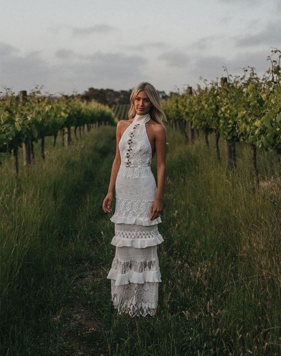 a whimsical boho sheath wedding dress with a halter neckline, layers and various types of detailing