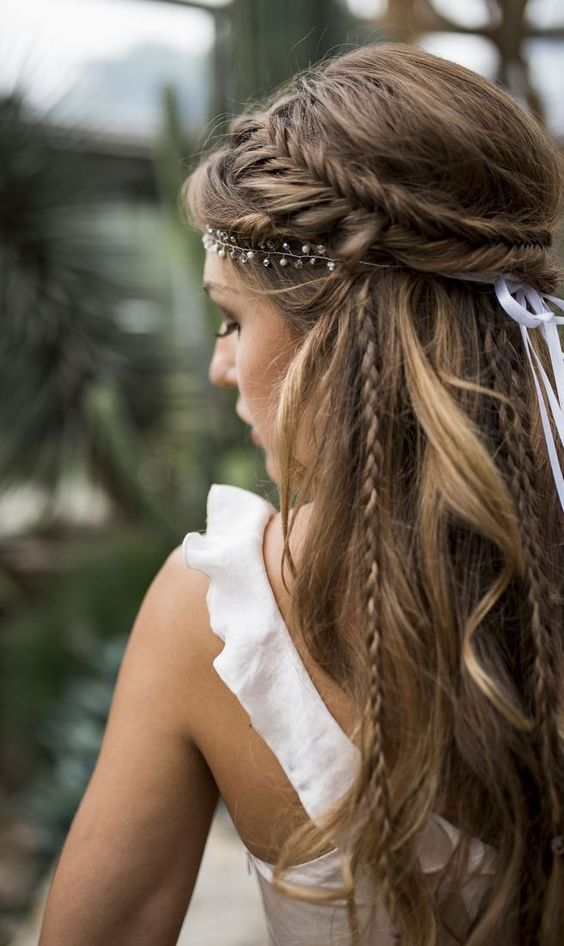 a whimsy and cool wedding hairstyle with a volume on top, a fishtail braid halo, some braids down and a rhinestone hairpiece
