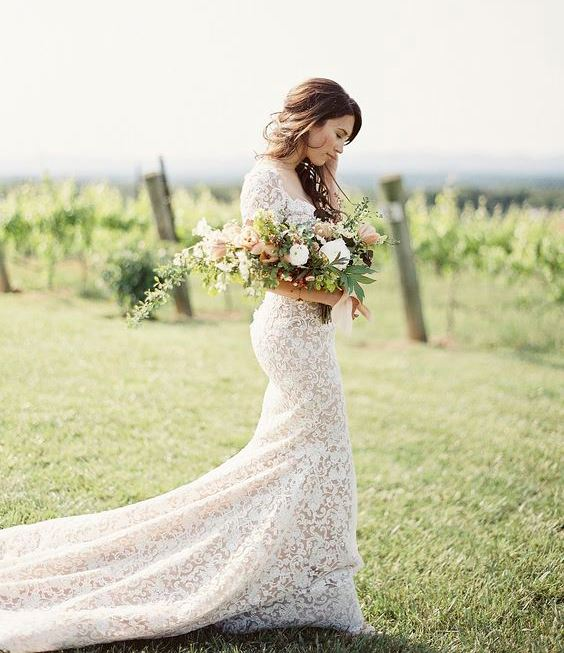 a white lace sheath wedding dress with a square neckline, short sleeves and a long train looks spectacular
