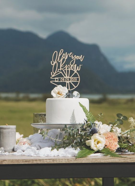 a white wedding cake with blooms and a lovely Star Wars topper - Millenial Falcon and a quote