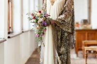 an art deco wedding dress with a neutral main dress, a gold embellished and applique neckline, super wide gold lace sleeves going dow to the floor