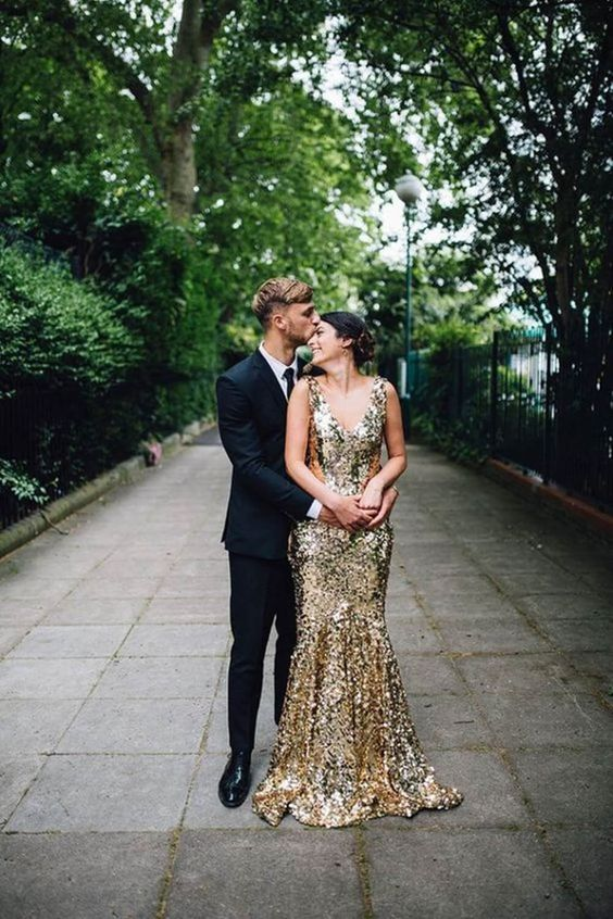 an elegant gold sequin mermaid wedding dress with wide straps and a short train is stylish and glam