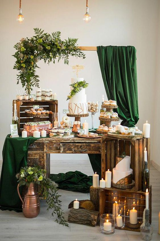 an elegant wedding dessert table of crates, lots of candles, a frame with greenery and dark green curtains and bulbs
