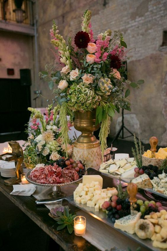 an ideal vineyard wedding cheese table with cheese, berries, salami and nuts plus lush florals for a vineyard wedding