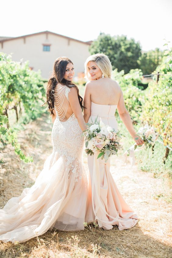 brides wearing blush mermaid wedidng dresses, one with chain back and white lace appliques, and the second of plain fabric and a layered tail
