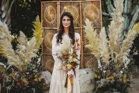a 70s boho wedding backdrop with a woven screen, bright blooms, greenery, pampas grass and layered rugs