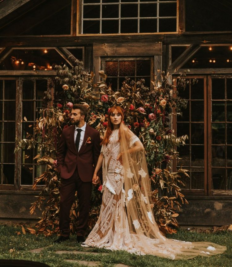 a beautiful fall floral wedding backdrop of greenery, blush and bold blooms plus dried leaves is a gorgeous idea for a fall wedding