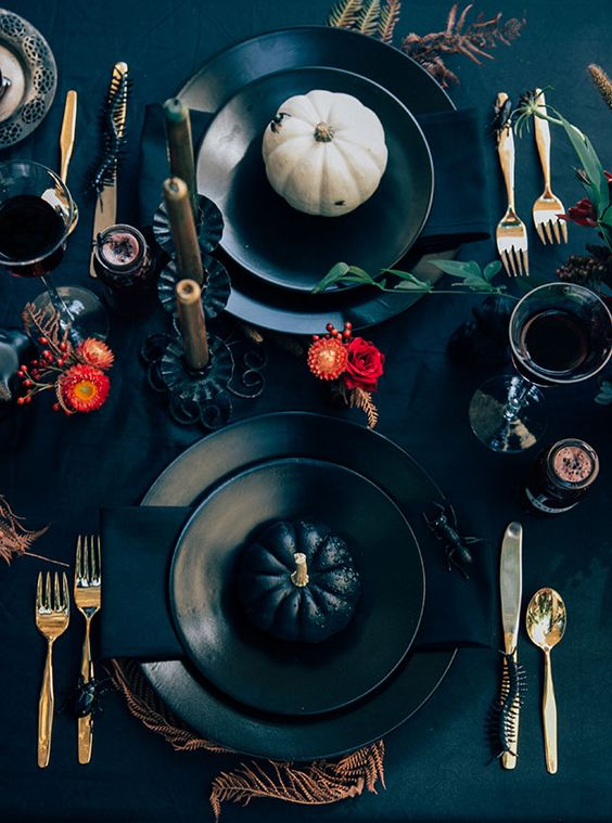 a black table setting with pumpkins, bright orange blooms, feathers and gilded touches is a gorgeous solution for a Halloween bridal shower