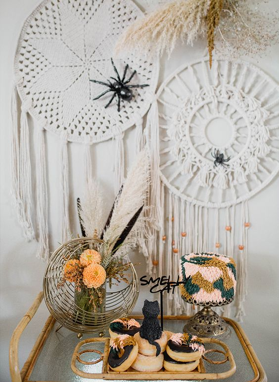 a boho Halloween bridal shower sweets table with a whimsical colorful fringe cake, glazed donuts with an edible cat and feathers