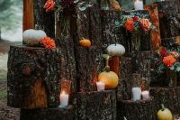 a boho fall wedding backdrop of tree stumps, pumpkins, gourds, bold blooms and candles is a gorgeous idea for a rustic fall wedding