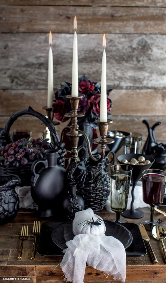 a bold Gothic table setting with dark blooms, tall and thin candles, black plates and jusgs, spiders is a stylish idea for a Halloween bridal shower
