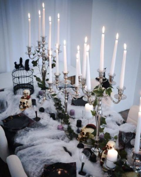 a bold Halloween bridal shower tablescape with spider web, tall and thin candles, black balls and skulls, a cage and black plates