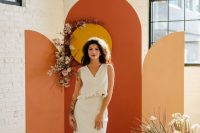 a bold boho fall wedding backdrop spruced up with blush blooms and fronds is a beautiful idea for a mid-century modern wedding