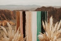 a bold boho fall wedidng backdrop of bright stripes and pampas grass arrangements is a cool and bright idea for a desert wedding