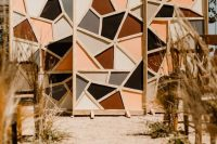 a bold fall geometric wedding backdrop and a wedding aisle lined up with dried grasses is a lovely idea for a mid-century modern wedding