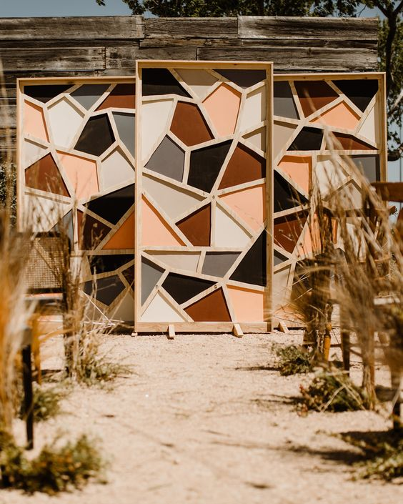 a bold fall geometric wedding backdrop and a wedding aisle lined up with dried grasses is a lovely idea for a mid century modern wedding