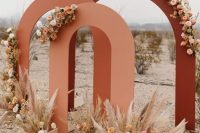 a bold fall wedding backdrop composed of three fall-colored arches, with neutral and pastel blooms and pampas grass for a boho wedding