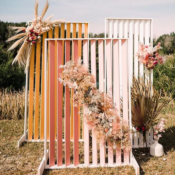 a bold fall wedding backdrop of mustard, pink and white planked pieces, pastel and neutral blooms, pampas grass and fronds is cool for a boho celebration