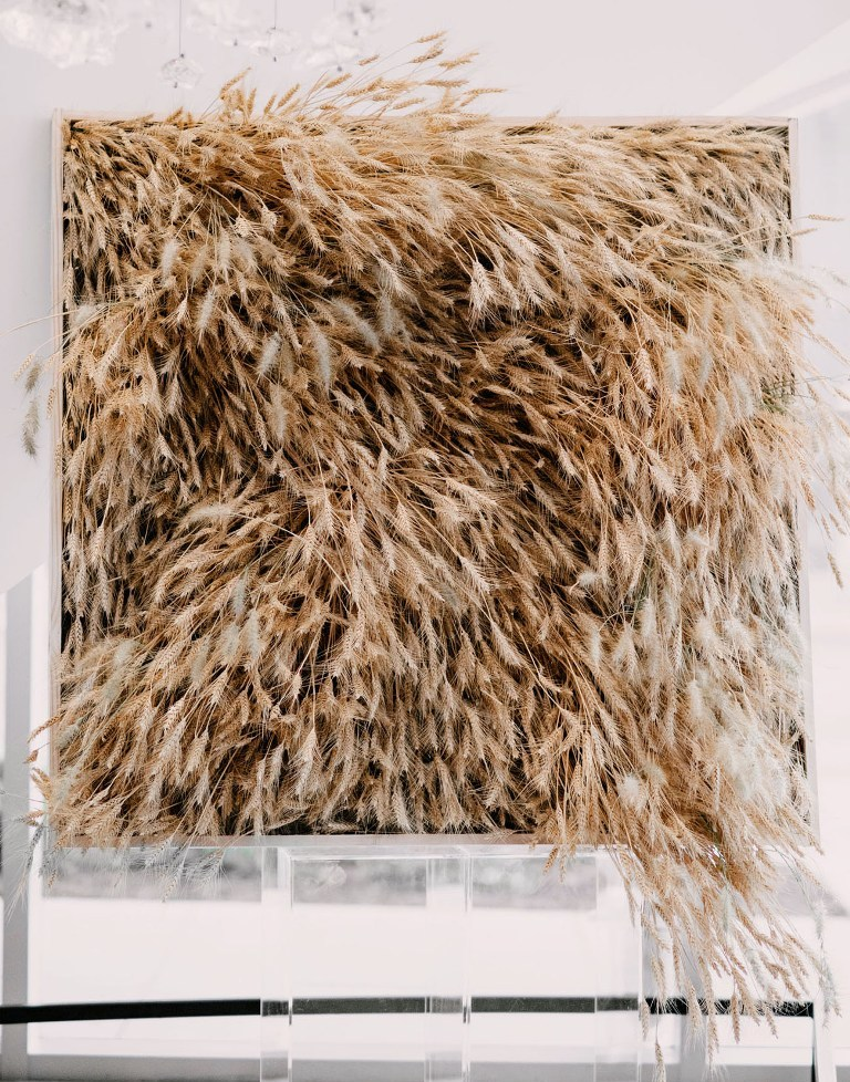 a bold mono floral wedding backdrop with wheat on an acrylic stand is a gorgeous modern rustic idea