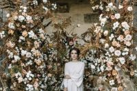 a cute wedding backdrop with dried leaves and blooms