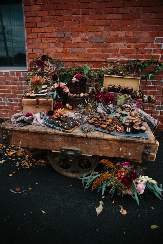 a bright fall dessert display of a large cart, bright blooms, greenery, moss and desserts and sweets