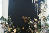 a catchy fall wedding backdrop in black spruced up with neutral and lilac blooms and greenery is a very eye-catchy idea to rock