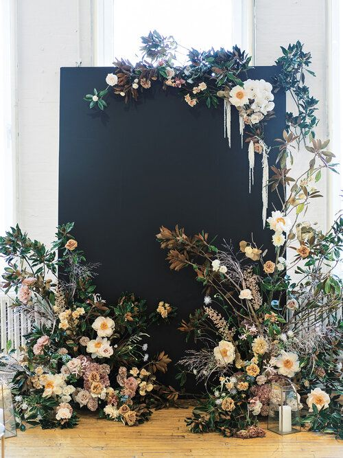 a catchy fall wedding backdrop in black spruced up with neutral and lilac blooms and greenery is a very eye catchy idea to rock