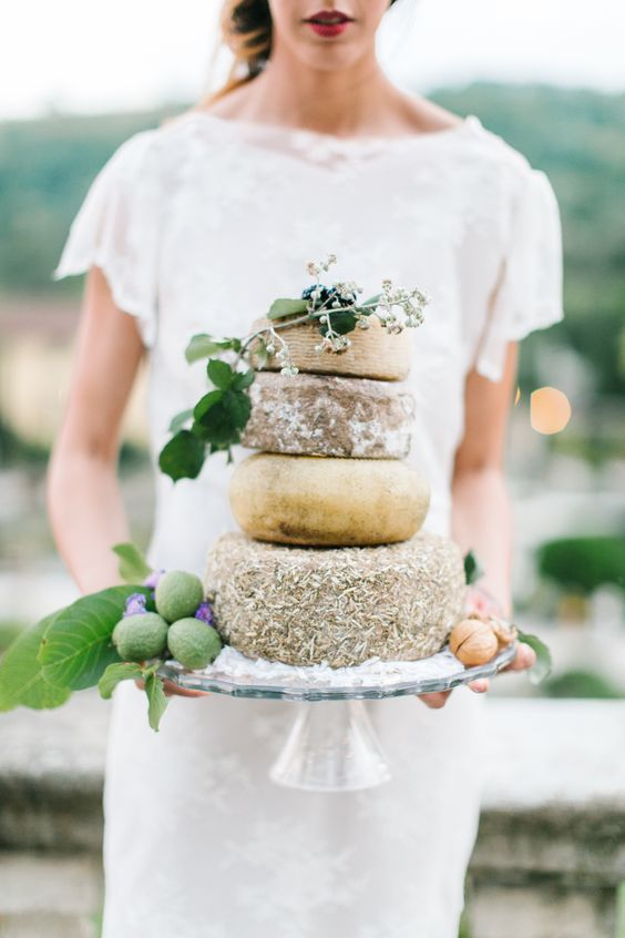 a cheese wheel cake with fresh fruits is a tasty alternative to a usual wedding cake for a couple who doesn't love sweets