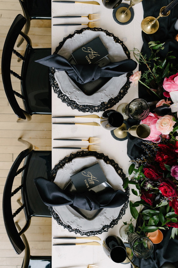 a chic Halloween bridal shower table setting with pink and red blooms and greenery, wire chargers, black napkins and glasses