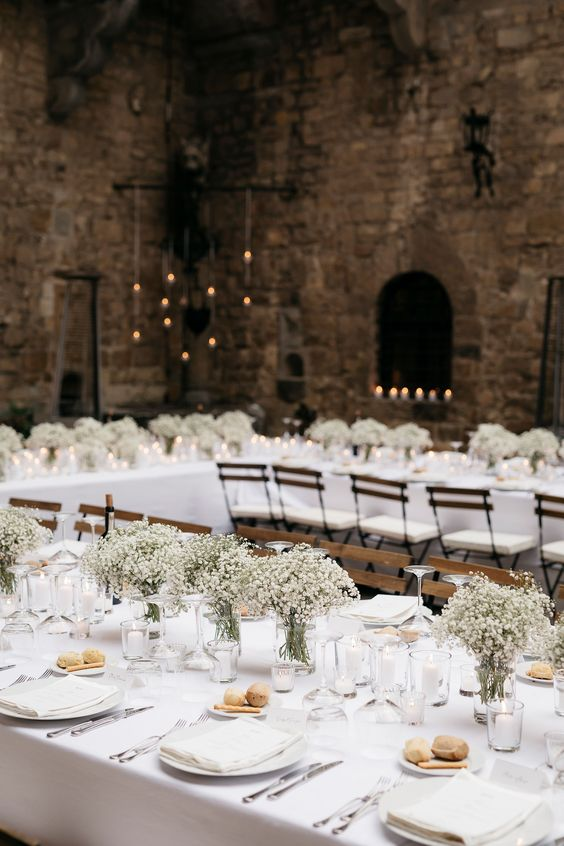 a classic Tuscany wedding tablescape with baby's breath, candles and white linens is pure elegance