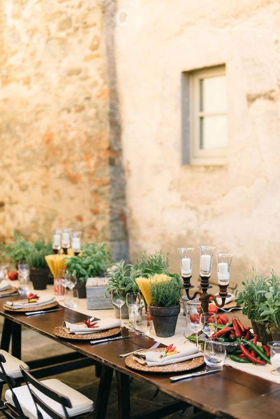 a cozy Tuscany wedding tablescape with potted herbs, spaghetti in jars, candles, fresh tomatoes and peppers and woven placemats