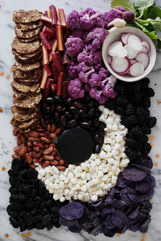 a dark Halloween inspired cheese bord with nuts, berries, veggies and dried fruit is a gorgeous idea for a vegetarian Halloween bridal shower