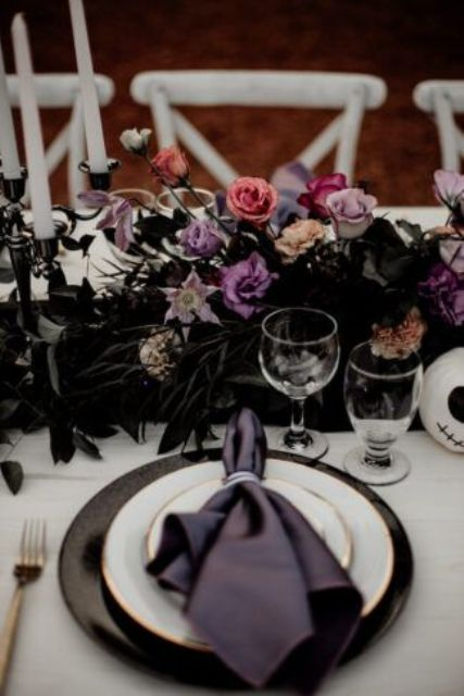 a decadent Halloween bridal shower tablescape with black, lilac, pink blooms and dark foliage, black chargers and purple napkins is amazing