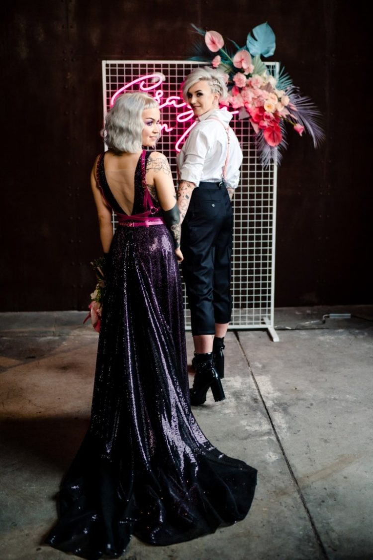 a deep purple sequin A-line wedding dress with thick straps, an open back, a train and pink belts for a bold look