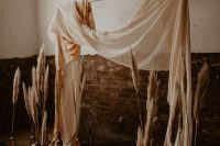 a fall boho lux wedding backdrop of neutral fabric and pampas grass in bottles is a gorgeous idea that is easy to compose