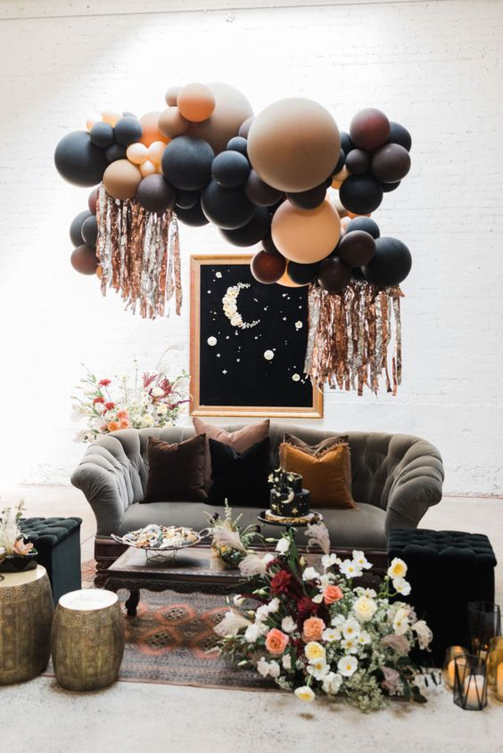 a gorgeous Halloween bridal shower lounge with dark balloons, lush florals and refined furniture is idea for your party